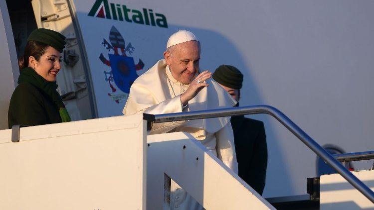 Pope Francis waves from the door of the Alitalia plane that is taking him to South America.